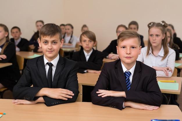 Счастливые школьники сидят за партой в классе