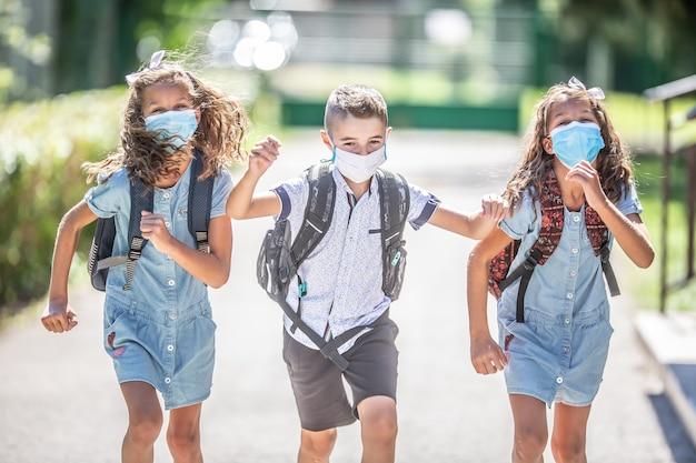 마스크를 쓴 행복한 학생들은 코비드-19 격리 기간 동안 학교로 돌아가는 기쁨에서 도망칩니다.