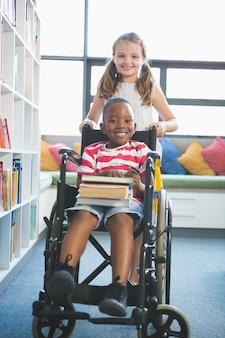 Happy schoolgirl carrying schoolboy in wheelchair