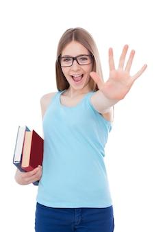 Счастливая школьница. счастливая девочка-подросток держит книги и протягивает ладонь, стоя изолированной на белом