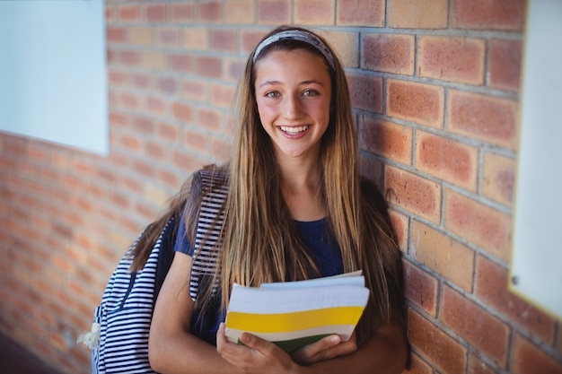 Happy schoolgirl holding books and standing near brick wall