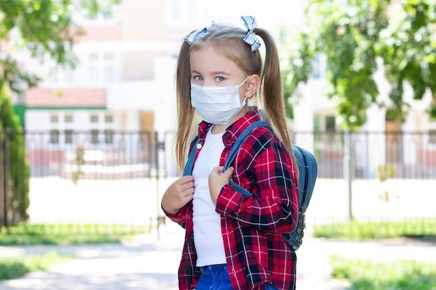 배낭과 보호 마스크에 행복 한 여 학생. 흰색 티셔츠와 체크무늬 셔츠에