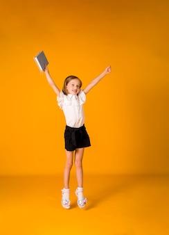 제복을 입은 행복한 여학생은 노란색 배경에 파란색 공책을 들고 공간 사본을 들고 점프합니다. 학교로 돌아가다
