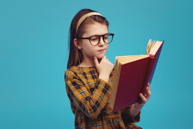 Счастливая школьница в очках читает книгу и делает домашнее задание Premium Фотографии
