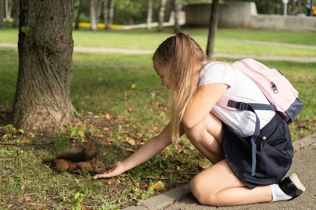 Счастливая школьница в форме с рюкзаком кормит белку в парке по дороге в школу.