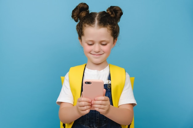 Happy schoolgirl isolated on blue studio wall hold smartphone look at screen smiling use internet online applications, play games, watch cartoons, wears yellow backpack, modern tech usage concept