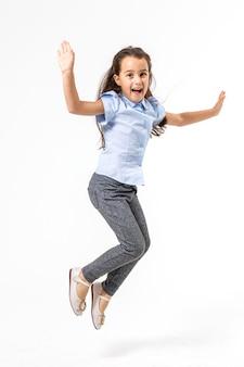 幸せな女子高生が白い背景の上で高くジャンプします。