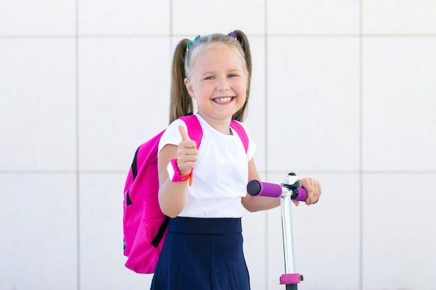 Счастливая школьница на скутере с рюкзаком