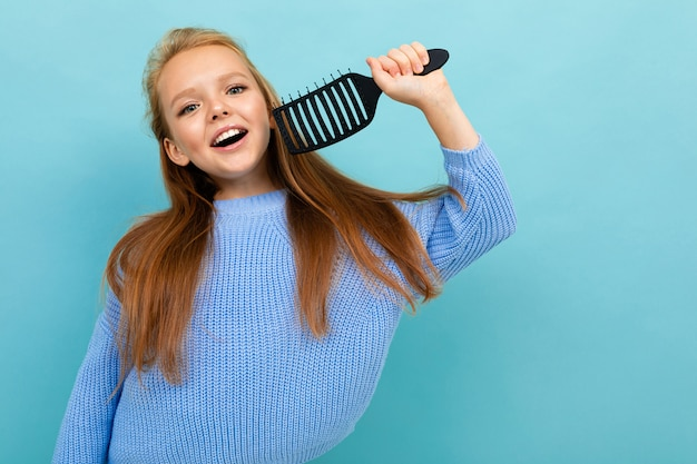 Happy schoolgirl posing on a blue background with a comb