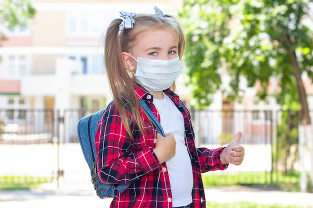 Happy schoolgirl in a protective mask with a backpack shows like. in a white t-shirt and a plaid shirt