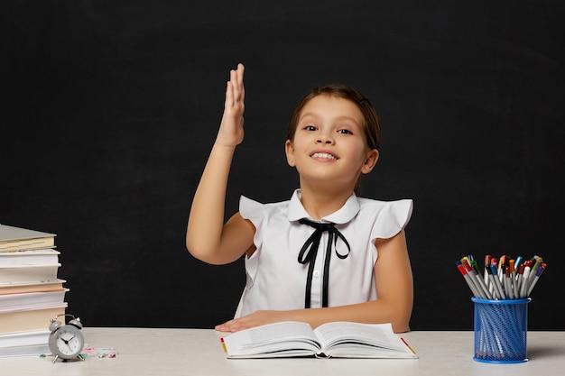 Счастливая школьница подняла руку, сидя за столом в классе на фоне доски