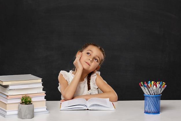 Счастливая школьница, сидя за столом в классе