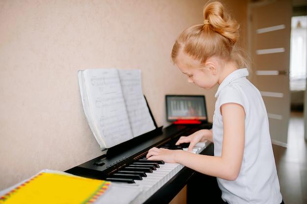 Счастливая школьница изучает ноты и играет на классическом цифровом пианино, смотрит онлайн-урок на планшете и учится играть на синтезаторе дома, самоизоляция, онлайн-обучение, дистанция