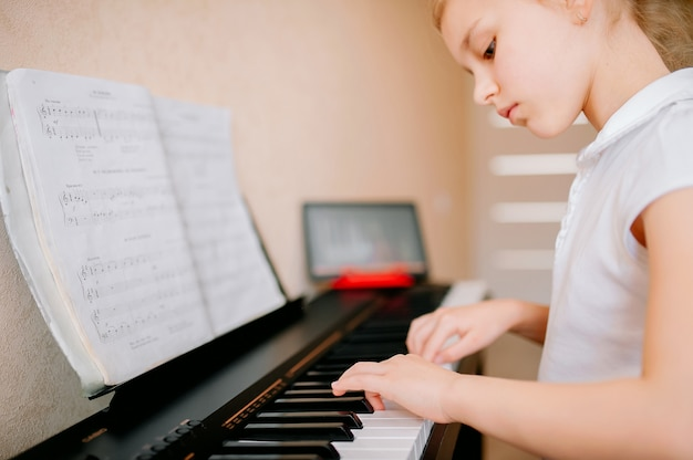 Happy schoolgirl studying notes and playing the classic digital piano while watching an online lesson on a tablet and learning to play the synthesizer at home, self-isolation, online education, distan