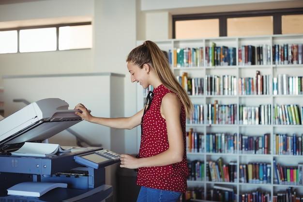 Happy schoolgirl using xerox photocopier in library
