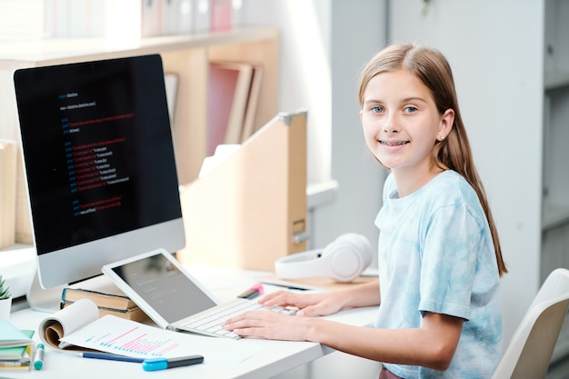 コンピューターの教室で机に座って、学校セミナーの準備をしながら幸せな女子高生