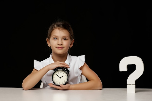 Счастливая школьница с будильником, сидя за столом