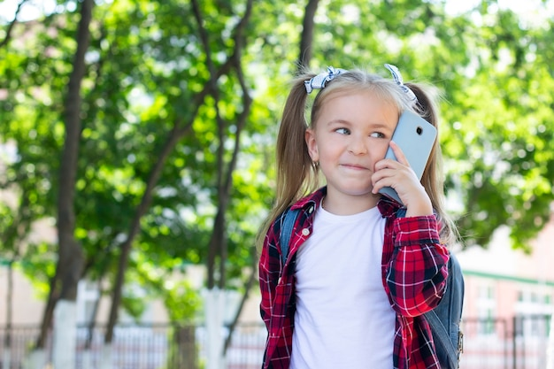 Happy schoolgirl with a backpack talking on the phone on the street. in a white t-shirt and a plaid shirt