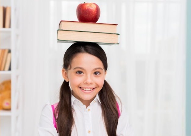 Happy schoolgirl with books and apple on head
