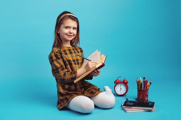 Счастливая школьница пишет в блокноте и сидит на синем фоне