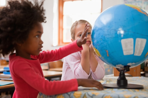 Happy schoolgirls looking at a globe