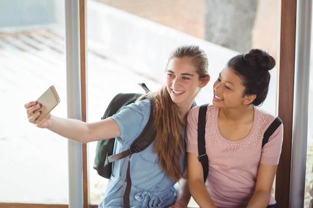 廊下で携帯電話でselfieを取って幸せな女子学生