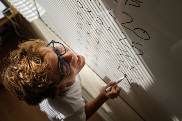 Happy schoolkid writing on whiteboard during math lesson