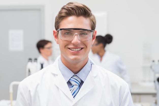 Счастливый ученый, улыбаясь на камеру с защитными очками