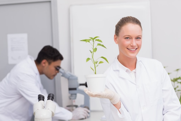 Happy scientist smiling at camera showing plant