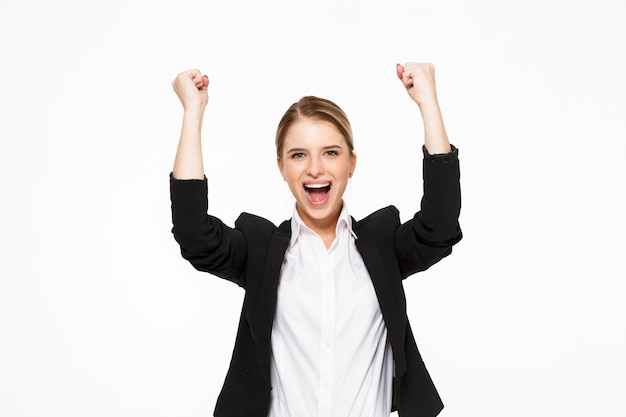 Happy screaming blonde business woman  over white wall