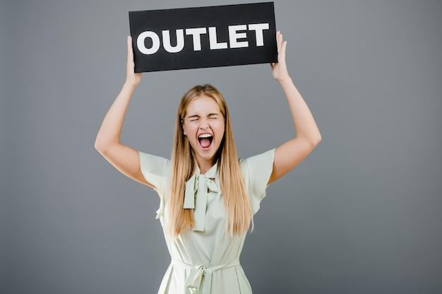 Happy screaming girl with outlet sign isolated over grey
