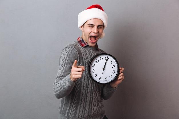 Счастливый кричащий мужчина в свитере и рождественской шляпе держит часы и указывает