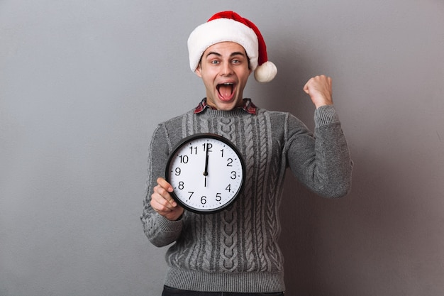 Счастливый кричащий мужчина в свитере и рождественской шапке держит часы и радуется