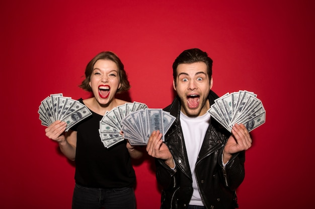 Happy screaming punk couple posing with money and rejoice