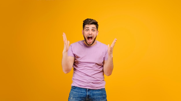 Happy screaming young man isolated over yellow background