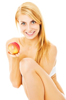 白い背景の上に孤立して座っている間リンゴを保持している幸せな半服の女性