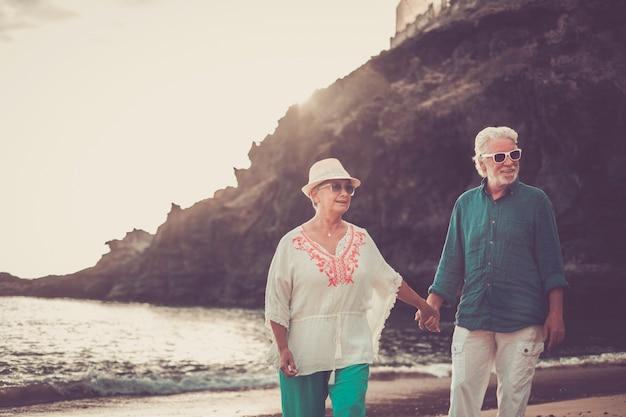ビーチで夏の時間を楽しみ、何年にもわたって仕事をした後、一緒に新しい人生の引退したライフスタイルを楽しみながら、手を振って微笑む幸せな老夫婦