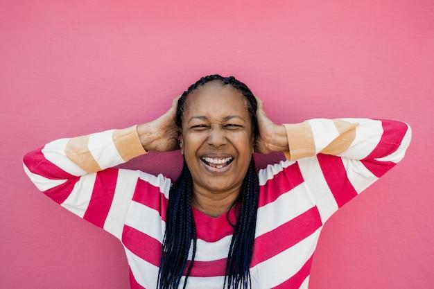 분홍색 배경을 가진 카메라를 보며 웃고 있는 행복한 고령의 아프리카 여성 - 얼굴에 초점