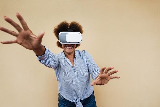 가상 현실 헤드셋을 사용하는 행복 수석 아프리카 여자-vr 고글에 초점