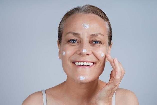 幸せな先輩は彼女の顔に化粧用クリームを塗ります。高齢者のスキンケアに直面します。