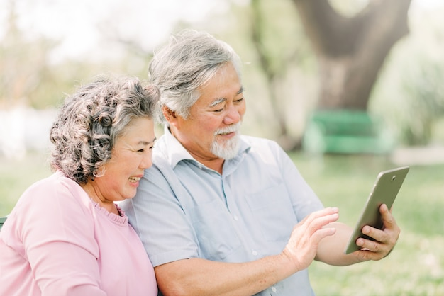 Happy senior asian couple using digital tablet