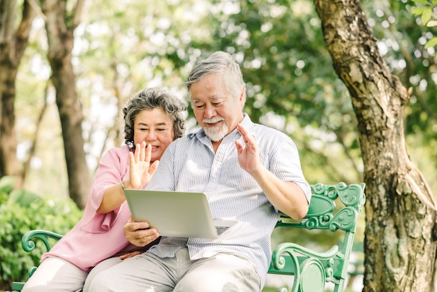 Happy senior asian couple waving hand to greet the love one while using laptop outdoor in the park