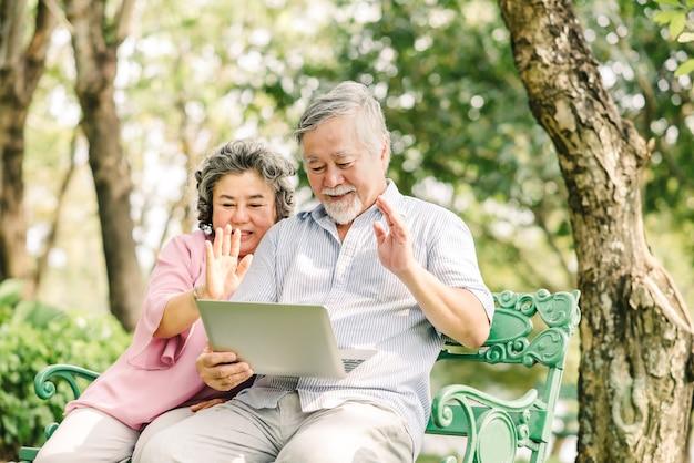 公園で屋外のラップトップを使用しながら愛する人に挨拶するために手を振って幸せなシニアアジアのカップル