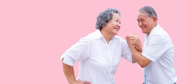 孤立した背景でダンスアクションで幸せなシニアアジアの祖父母