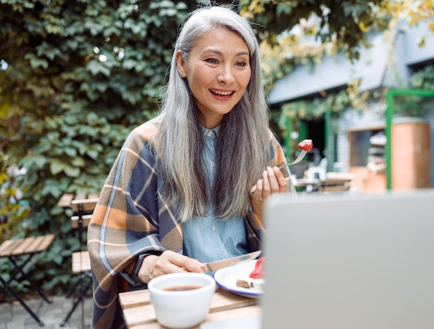 Happy senior asian lady eats toast with strawberries watching video via laptop at table outdoors