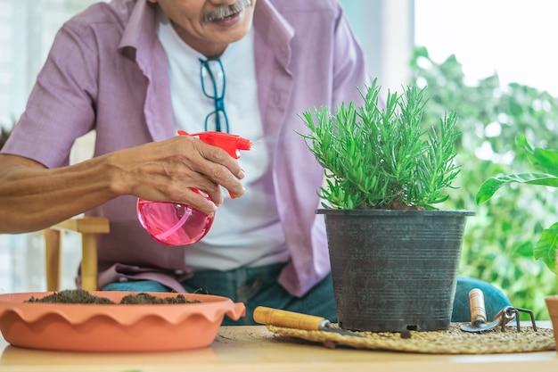 幸せなシニアアジアの引退した男が植木鉢に水を噴霧しています