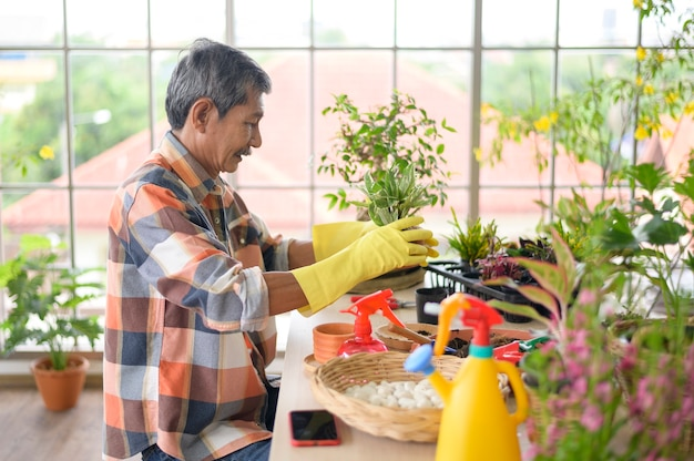 A happy senior asian retired man spraying and watering tree  enjoys  leisure activity at home