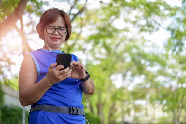 Happy senior asian woman holding smart phone with listening to music