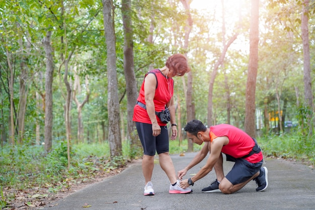 Happy senior asian woman with man or personal trainer tying shoe laces in the park
