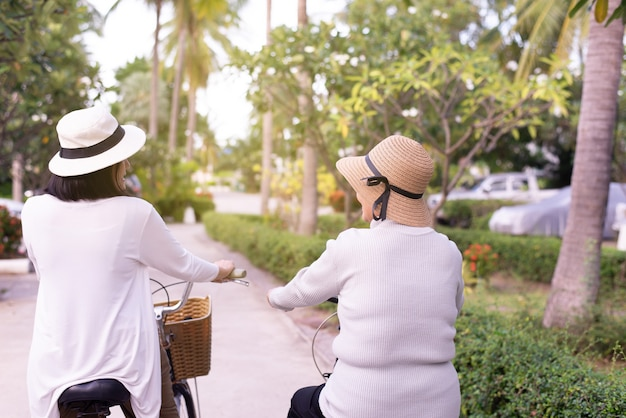 행복 한 고위 아시아 여성 자전거 공원에서 딸과 함께 자전거